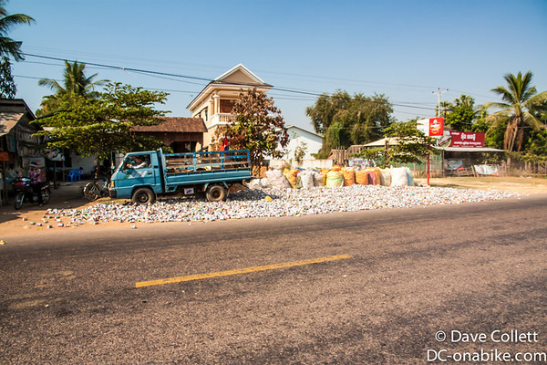 Crushing cans in Cambodia- driving your truck backwards and forwards over them!